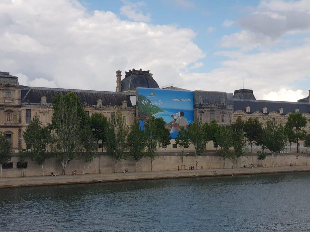 La valla que promociona a República Dominicana como destino turístico en una de las paredes exteriores del Louvre, en París, Francia.
