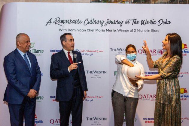 María extrae la tarjeta del ganador de la rifa de dos billetes en clase ejecutiva donados por Qatar Airways.